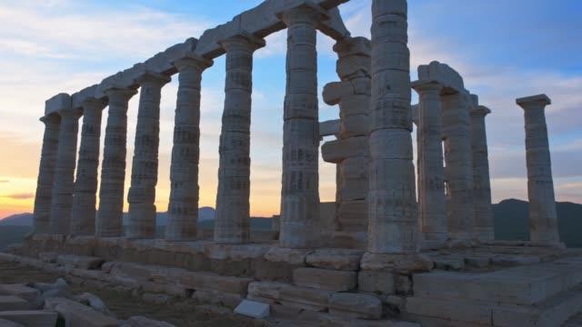 Poseidon temple ruins on Cape Sounio on sunset, Greece Greece Cape Sounio. Ruins of an ancient temple of Poseidon, Greek god of the sea, on sunset. Pan shot of temple ruins on sunset. Tourist landmark of Attica, Sounion, Greece sounion stock videos & royalty-free footage