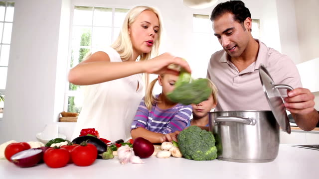Posing family putting vegetables in a pot video