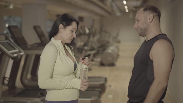 stockvideo's en b-roll-footage met positieve volwassen man en vrouw die in gymnastiek spreken en lachen. zijaanzichtportret van atletisch sportief kaukasisch paar dat in geschiktheidsclub flirt. levensstijl, sport, atletisch, relatie. - flirten