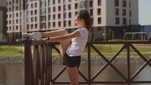 Positive athletic woman in a T-shirt,shorts and sneakers doing a leg stretch on the pier on the shore of pond.Sports healthy lifestyle.Outdoor training.Urban landscape in the background.