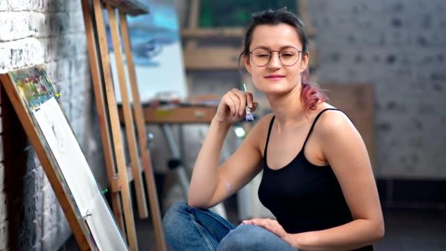 vídeos y material grabado en eventos de stock de positiva hermosa joven pintor mujer posando en el estudio de arte durante el trabajo medio tiro - imagen pintada