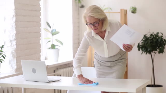 Positive businesswoman prepares her workplace wipes table with rag Aged businesswoman holds rag wipes workplace desk prepares for workday negotiation meeting with client, to keep clean up table office room, healthy safety no dust, starts finish productive day concept cleaning stock videos & royalty-free footage