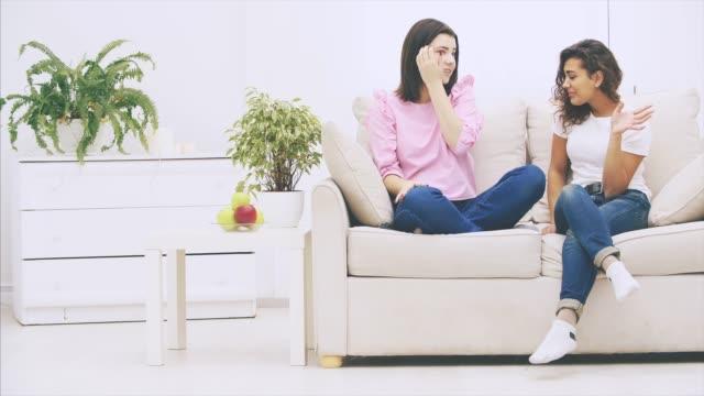 positiva kaukasiska och afro-amerikanska flickor sitter på soffan, pratar och gest vänliga och känslomässigt, leende. - kvinna ventilationssystem bildbanksvideor och videomaterial från bakom kulisserna