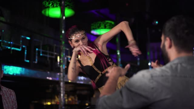 Positive Caucasian woman with red hair dancing on stage and smiling to visitors. Professional young go go dancer working in night club. Profession, occupation, lifestyle. Positive Caucasian woman with red hair dancing on stage and smiling to visitors. Professional young go go dancer working in night club. Profession, occupation, lifestyle. dyed red hair stock videos & royalty-free footage