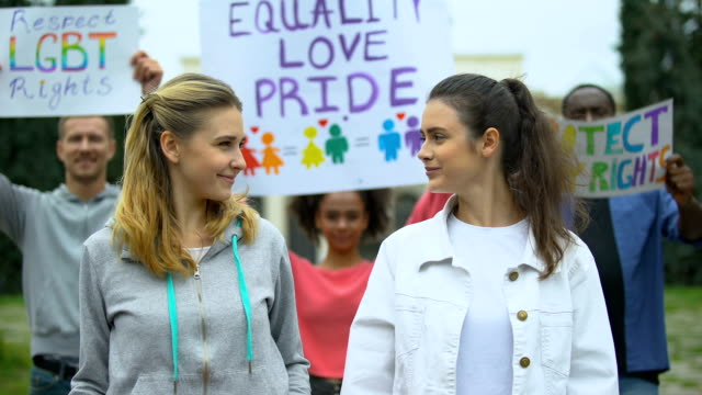 Positive crowd raising rainbow symbols and posters for LGBT rights, pride march Positive crowd raising rainbow symbols and posters for LGBT rights, pride march lgbtqi rights stock videos & royalty-free footage