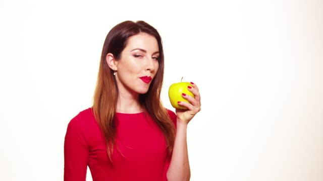 Positive weibliche beißen großer grüner Apfel Obst lächelnd Weißer Hintergrund – Video