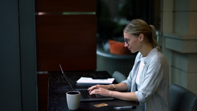 Positive female copywriter typing text for funny article on content website enjoying remote work and good internet connection on laptop computer