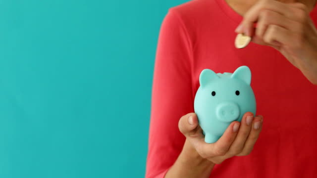 Positive female putting coin in piggybank, planning budget, financial savings Positive female putting coin in piggybank, planning budget, financial savings on blue background piggy bank stock videos & royalty-free footage