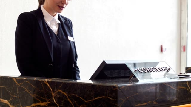 Positive female receptionist typing on computer video