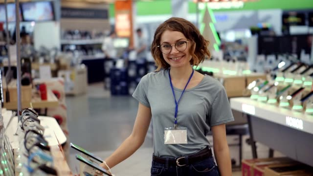 Positive female seller or shop assistant portrait in supermarket store. Woman in blue shirt and empty badge looking at the camera and smiling. Electronic devices on the background. Slow motion