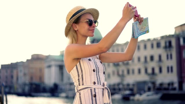 positive female tourist in stylish hat making photos for posting in travel web blog using smartphone camera during italian summer  holidays - cartina italia video stock e b–roll