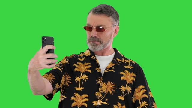 Positive funny funky old man making selfie on a Green Screen, Chroma Key