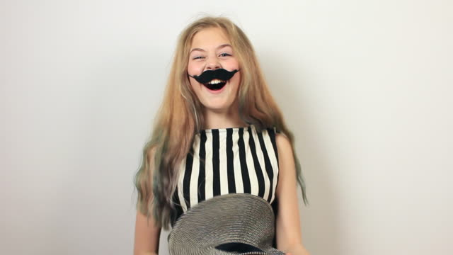 positive girl with fake moustache having fun. - april fools day stock videos and b-roll footage