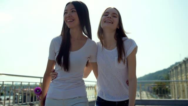 positive girls walking against urban background - chudy filmów i materiałów b-roll