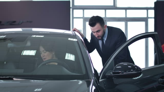 Positive handsome male dealer consulting successful businesswoman sitting on driver's seat. Caucasian man selling new vehicle to confident adult woman. Cinema 4k ProRes HQ.