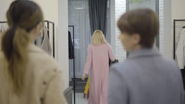vídeos y material grabado en eventos de stock de mujer feliz positiva mostrando blusa amarilla a los amigos en el centro comercial y dejando al vestidor. retrato de la hermosa rubia segura comprador comprando ropa en el viernes negro. - black friday sale