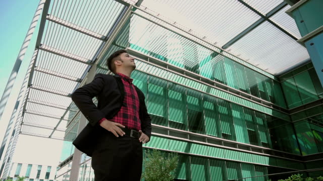 Positive Indian young businessman looking at buildings video