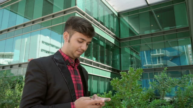 Positive Indian young man walking along office building texting video