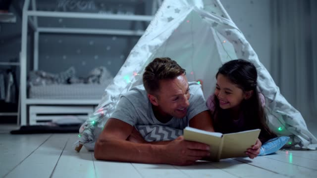 Positive little girl and her father reading a book together video