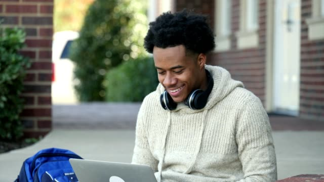 vídeos de stock e filmes b-roll de positive male college student uses laptop on campus - roupa desportiva