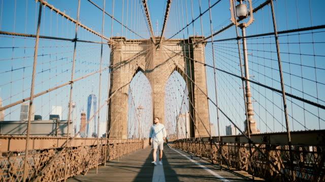 positive male european tourist walking towards camera, smiling and looking around along brooklyn bridge, new york 4k - city walking background video stock e b–roll