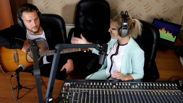positive man in headphones playing guitar next to girl radio host indoors video