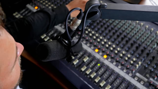 positive man in headphones speaks into microphone and makes sound louder on equipment in radio studio video