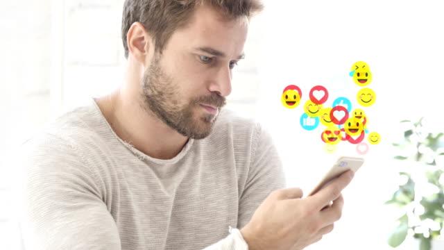 positiver mann mit smartphone, fliegenden emojis, smileys und likes - smiley stock-videos und b-roll-filmmaterial