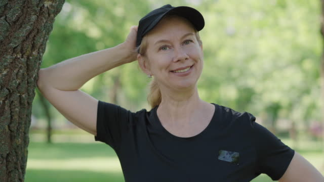 Positive mid-adult sportswoman in black sportswear and cap standing in sunny summer park and smiling at camera. Happy Caucasian woman posing outdoors after training. Workout, sport, fitness. Positive mid-adult sportswoman in black sportswear and cap standing in sunny summer park and smiling at camera. Happy Caucasian woman posing outdoors after training. Workout, sport, fitness. one mid adult woman only stock videos & royalty-free footage