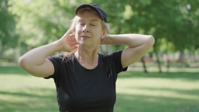 positive mittel-erwachsenen-sportlerin auf kappe setzen und verlassen. porträt der selbstbewussten kaukasischen blonden frau in sportbekleidung im sonnigen sommerpark. aktiver lebensstil der glücklichen dame. sport und gesunder lebensstil. - einzelne frau über 30 stock-videos und b-roll-filmmaterial