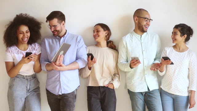 Positive multiracial millennial people holding electronic gadgets standing against wall
