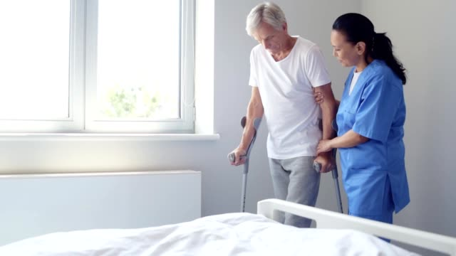 Positive nurse helping an aged man to walk on crutches I will support you. Pleasant positive nurse helping a senior man to walk on crutches while staying in a hospital ward crutch stock videos & royalty-free footage