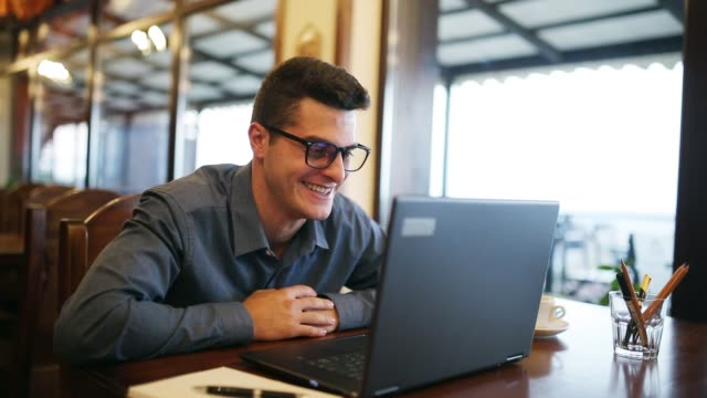 Positive smiling caucasian man in glasses talking on video conference call chat with a laptop in cafe. Speaker holds online masterclass. Male communicating with relatives girlfriend and friends video