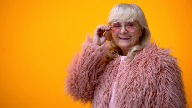 positive smiling senior lady in pink coat and round sunglasses winking, flirt - espressione del viso video stock e b–roll