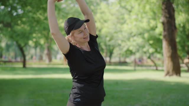 Positive sportswoman exercising on fresh air on sunny day. Portrait of smiling mid-adult Caucasian woman training in summer park outdoors. Healthy lifestyle, sport, fitness. Positive sportswoman exercising on fresh air on sunny day. Portrait of smiling mid-adult Caucasian woman training in summer park outdoors. Healthy lifestyle, sport, fitness. one mid adult woman only stock videos & royalty-free footage