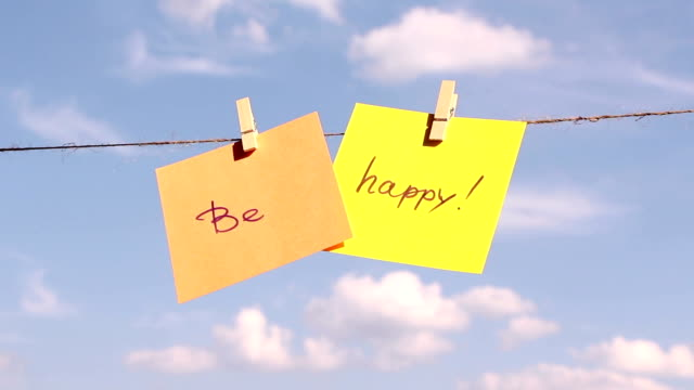 """Positive thinking concept.  """"be happy"""" sentence """"be happy"""" on colorful paper pinched on a rope. Positive thinking concept. pinching stock videos & royalty-free footage"""