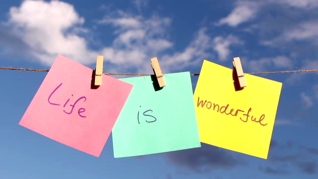 """Positive thinking concept.""""Life Is Wonderful"""" sentence """"Life Is Wonderful"""" on colorful paper pinched on a rope. Positive thinking concept. pinching stock videos & royalty-free footage"""