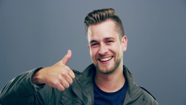 Positive thinking is all you need 4k video footage of a young man showing thumbs up against a grey background representing stock videos & royalty-free footage
