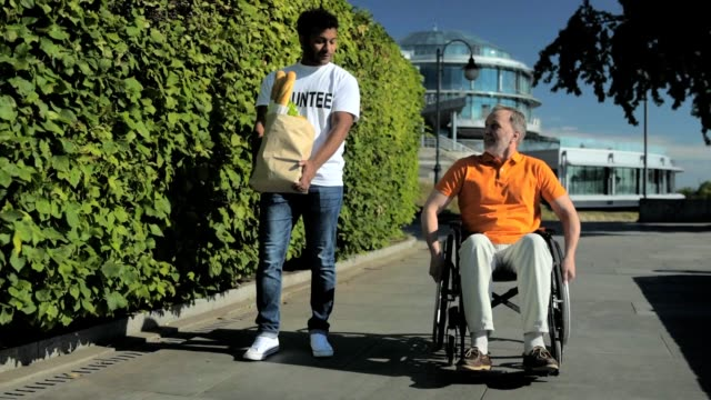 positive volunteer helping wheelchaired man with carring products - sostegno video stock e b–roll