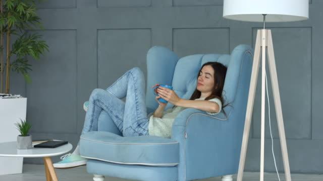 Positive woman enjoying morning coffee in armchair