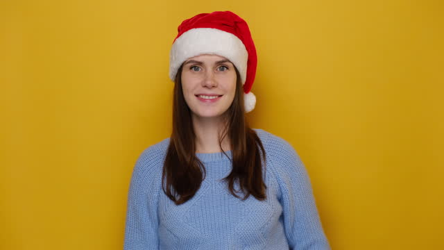 Positive young female in Christmas red hat, has toothy smile, makes hush gesture, wears cozy blue sweater, poses against yellow studio wall with copy space for advertisement. Happy New Year concept