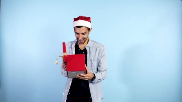 vídeos de stock e filmes b-roll de positive, young guy in christmas hat and garland on neck recieves surprise from from the side female hands - being in good festive mood, isolated over blue background. people, surprisment and presents concept - gift box