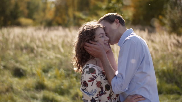 positive young happy loving couple walking on meadow in summer holding hands. - rappresentazione umana video stock e b–roll