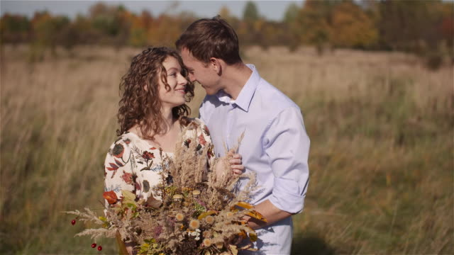 positive young happy loving couple. young woman holding flowers in hands. - rappresentazione umana video stock e b–roll