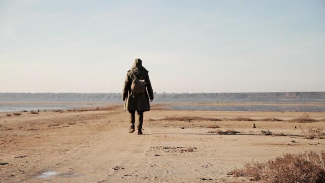 vídeos de stock e filmes b-roll de post apocalypse lonely man walks on the wasteland - apocalipse
