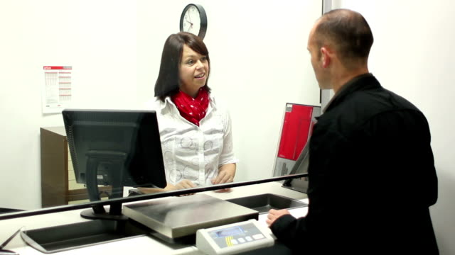 Post Office - Handing out a form Stock HD video clip footage of a Post Office clerk handing out a form to a customer post office stock videos & royalty-free footage