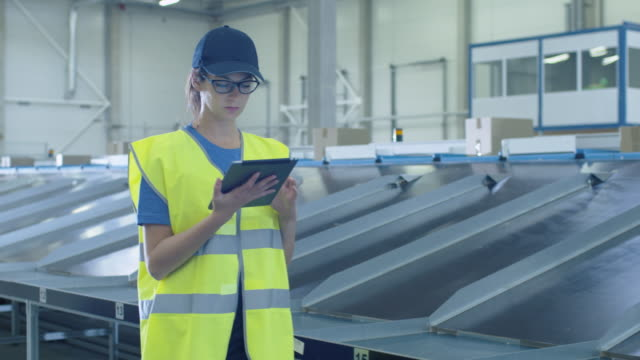 Post Sorting Center Female Worker Walking Along Conveyor while Using Tablet Computer. video