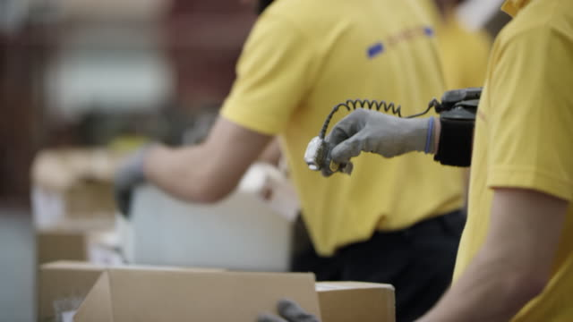 Postal employees scanning packages with wearable ring barcode scanner Medium handheld shot of a postal employees scanning parcels on the conveyor belt with a wearable ring barcode scanner. Shot in Slovenia. production line worker stock videos & royalty-free footage