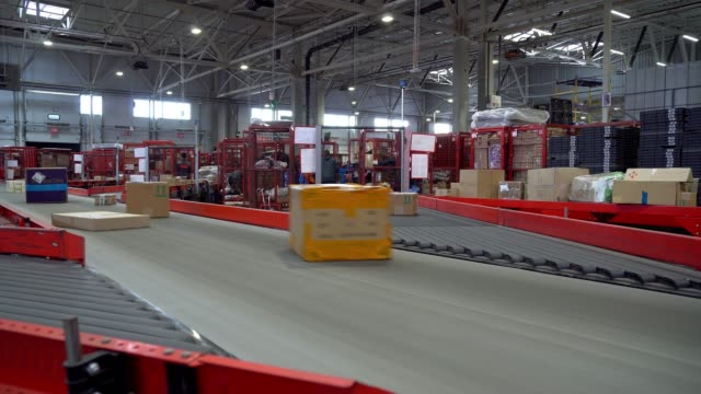 Postal Parcel Sorting Line Postal Conveyor System, Parcels are Moving on Belt Conveyor at Post Sorting Office satisfaction stock videos & royalty-free footage