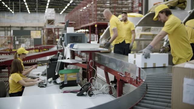 ds postangestellten scannen pakete und stapeln sie in das flugzeug versandbehälter - arbeiter stock-videos und b-roll-filmmaterial